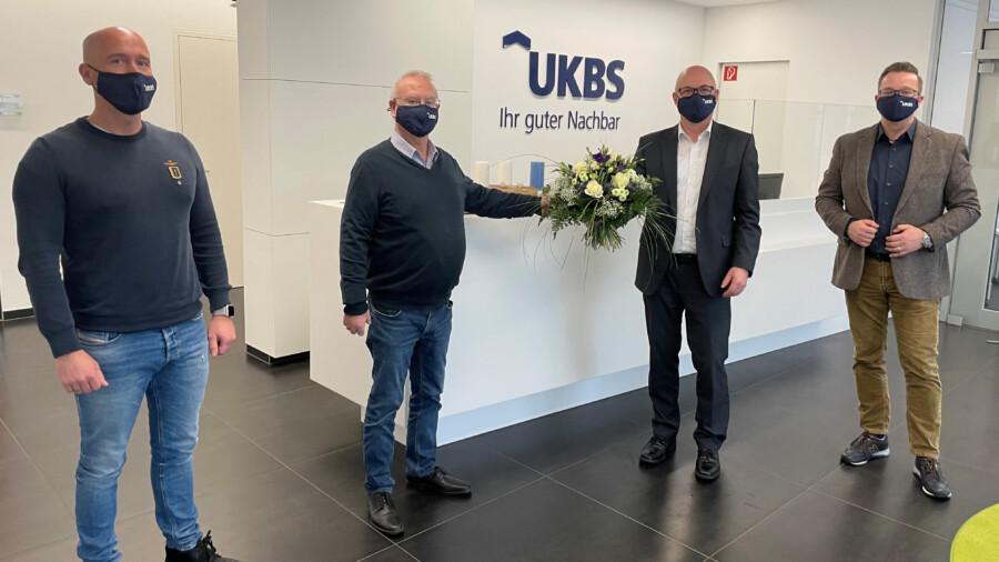 Die  Prokuristen Alexander Krawczyk (li.) und Marton Kolander (re.) sowie Aufsichtsratsvorsitzender Theo Rieke (2.v.li.) gratulieren UKBS-Geschäftsführer Matthias Fischer zum 30-jährigen Dienstjubiläum. (Foto: UKBS)