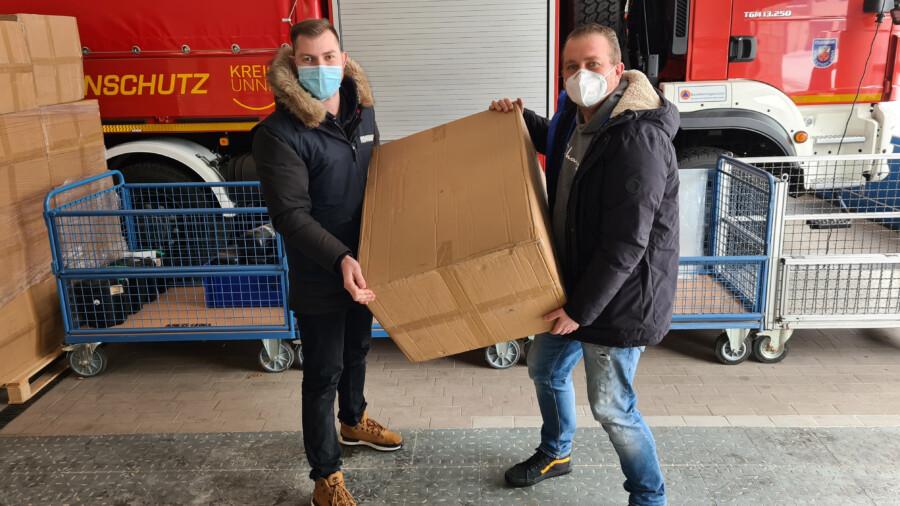 Kai Proske vom Bevölkerungsschutz des Kreises, hier mit Rudolf Meisner vom Ordnungsamt der Stadt Werne, beim Verladen der Masken für die Leistungsempfänger. (Foto: Patrick Isken - Kreis Unna)
