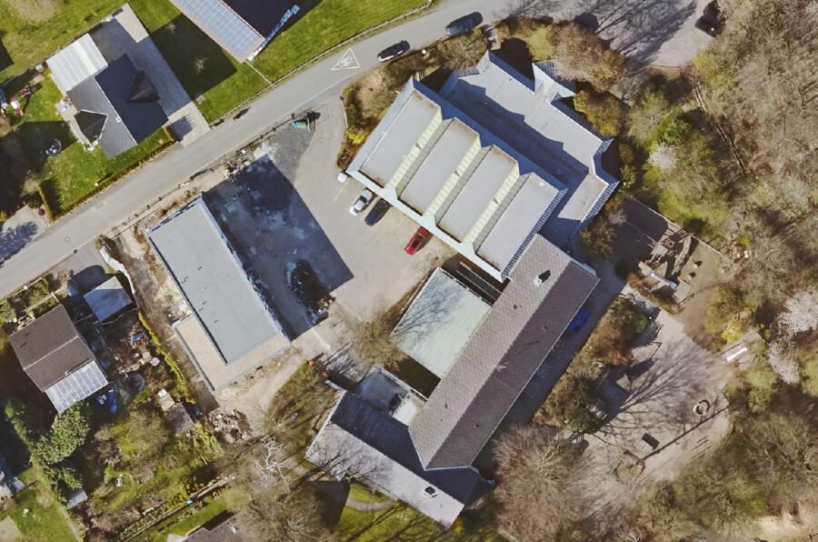 Diese Aufnahme zeigt die Paul-Gerhardt-Schule aus der Vogelperspektive. Der Planungsbereich für die Neugestaltung der Außenanlagen erstreckt sich auf den Park- und Vorßplatz in der Mitte der Gebäude sowie das Umfeld des OGS-Gebäudes (graues Flachdach links). (Luftbild: geoservice-kreis-unna.de)
