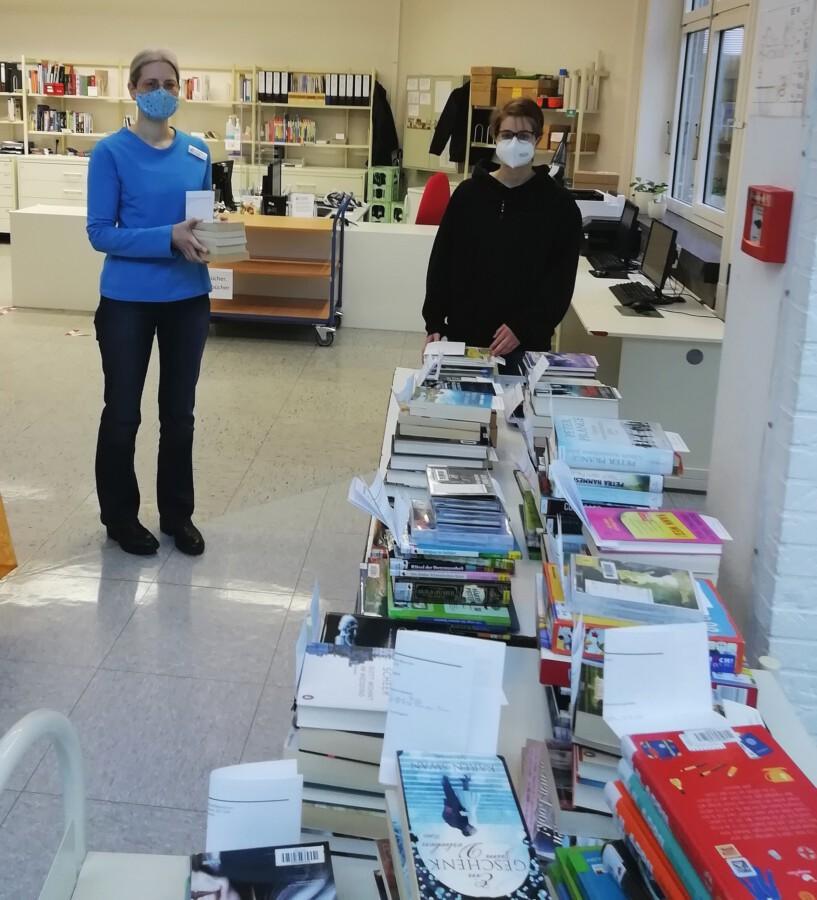 Büchereileiterin Kristina Truß und FSJlerin Mascha Wöstmann (r.) bereiten die Medien zur Abholung in der Bibliothek vor. Mascha Wöstmann hat auch dem Newesservice der Bücherei  ein neues Design verpasst. (Foto: Gemeinde Holzwickede)