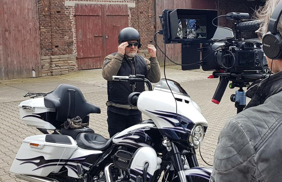 Pfarrer Uwe Rimbach setzt den Helm auf für die nächste Fahrt während des Drehs zum Motorradgottesdienstes.. (Foto: Ev. Kirchenkreis Unna)