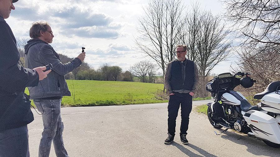 Pfarrer Uwe Rimbach hat nebenseiner Harley Platz genommen, Kamera und Ton werden von Jörn Spiegelberg und Dietrich Schneider überwacht. (Foto: Ev. Kirchenkreis Unna)
