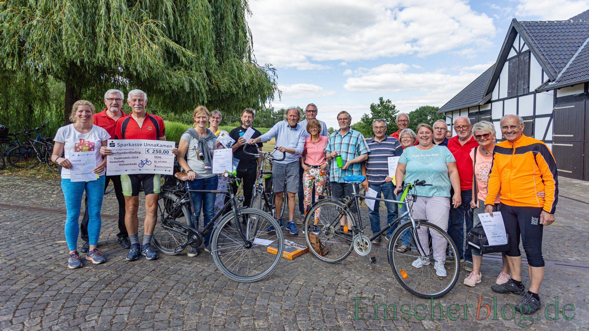 Die Umweltberauftragte der Gemeinde, Tanja Flormann (5.v.re.) hält für die Teams des gerade gestarteten Stadtradeln-Wettbewerbs die grünen Lenkerbändchen bereit: Die erfolgreichen Stadtradler des Jahres 2019 nach der Preisverleihung. (Foto: P. Gräber - Emscherblog)