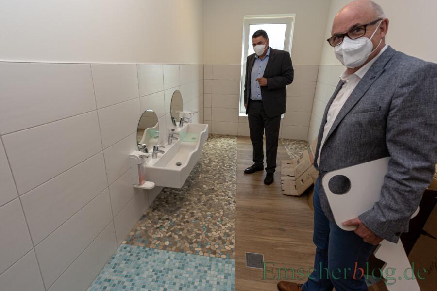UKBS-Geschäftsführer Matthias Fischer (re.) und Landrat Mario Löhr in einem der Bäder, die mit wellenförmigen Waschbecken in unterschiedlicher Höhe und originellen Mosaikböden ausgestattet sind. (Foto: P. Gräber - Emscherblog)