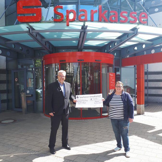 Der Leiter der Sparkasse Holzwickede, Dirk Röller, überreicht der Stadtradeln-Koordinatorin Tanja Flormann einen symblischen Spendenscheck über 250 Euro. (Foto: Gemeidne Holzwickede)