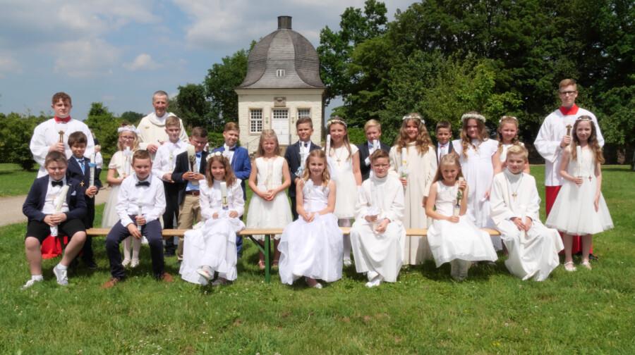 Nach langer Wartezeit konnte am vergangenen Sonntag endlich die gemeinsame Erstkommunion gefeiert werden: Die 21 Kommunionklinder mit Pastor Berndhard Middelanis und zwei Messdienern im Park von Haus Opherdicke. (Foto: Wolfgang Nowak)