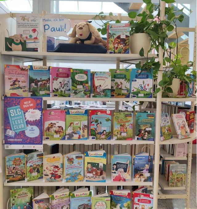 Bibliotheks-Maskottchen Pauli sitzt im Eingangsbereich der Gemeindebücherei auf dem Regal mit den neuen Kinderbüchern. Die bücher können selbstverständlich auch für den Sommerleseclub ausgeliehen werden (Foto: (Gemeinde Holzwickede)