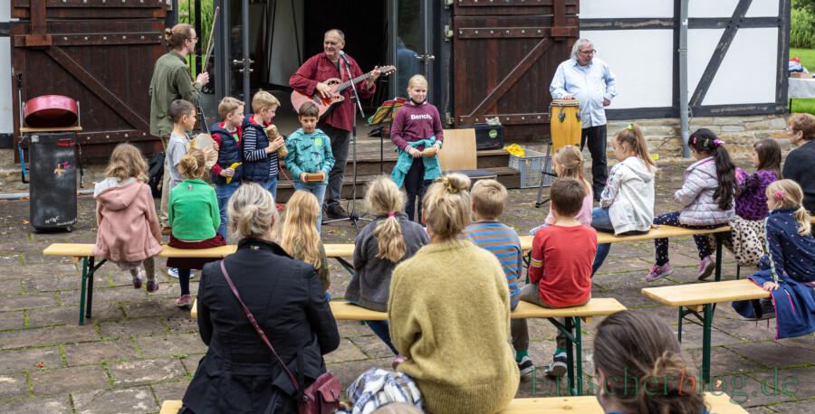 Uli Bär (m. Gitarre) und sein Team der Jugendkunstschule Unna nahmen die Grundschulkinder am Samstag auf dem Enscherquellhof mit auf eine Entdeckungsreise mit Musik, Kunst und Tanz. (Foto: P. Gräber - Emscherblog)